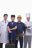 Porträt glücklichen und lächelnden Doktors, des Luft-Stewardesses, des Bauarbeiters und der Chef-Atelieraufnahme Lizenzfreie Stockfotos