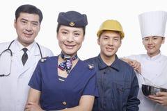 Porträt glücklichen und lächelnden Doktors, des Luft-Stewardesses, des Bauarbeiters und der Chef-Atelieraufnahme Lizenzfreies Stockfoto