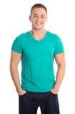 Porträt: Glücklicher lokalisierter junger Mann, der grünes Hemd und Jeans trägt stockfotografie