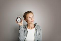 Porträt-hübsche junge Frau, die leeren Gray Background aufwirft Hübsches Mädchen, das Weinlese-Wecker-Hand leer halten lächelt stockfotografie