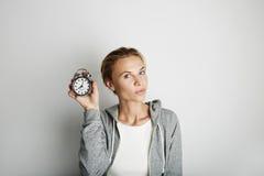 Porträt-hübsche junge Frau, die leeren weißen Hintergrund aufwirft Hübsches Mädchen, das Weinlese-Wecker-Hand leer halten lächelt Lizenzfreie Stockfotografie