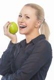Porträt hübsche und glückliche blonde Frau-beißender grüner saftiger APP Lizenzfreie Stockfotos