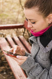 Porträt hübscher Mode blondie Frau, die Handy betrachtet Glänzendes Lächeln Stockfotos