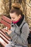 Porträt hübscher Mode blondie Frau, die Handy betrachtet Glänzendes Lächeln Stockbilder