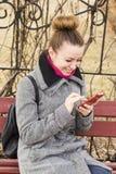 Porträt hübscher Mode blondie Frau, die Handy betrachtet Glänzendes Lächeln Lizenzfreie Stockfotos