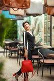 Porträt im Freien der Abkürzung Brunettefrau in der stilvollen Klage und in der roten Tasche, modische Sommerausstattung, die im  lizenzfreies stockfoto