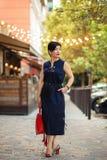 Porträt im Freien der Abkürzung Brunettefrau im stilvollen Kleid und in der roten Tasche, modische Sommerausstattung, die im Café lizenzfreie stockfotos