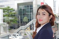Porträt im Freien der glücklichen jungen asiatischen Geschäftsfrau, die Kamera im Stadthintergrund betrachtet Stockfoto
