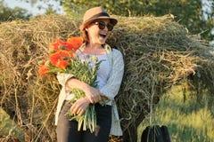 Porträt im Freien der glücklichen reifen Frau mit einem Blumenstrauß von roten Blumen der Mohnblumen stockfotografie