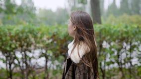 Porträt im Freien der jungen schönen modernen Frau, die in der Straße aufwirft Vorbildlicher tragender stilvoller brauner Mantel  stock video footage