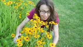 Porträt im Freien der jungen schönen modernen Frau riecht gelbe Blumen stock footage