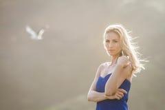 Porträt im Freien der jungen Schönheit im blauen Kleid, das an aufwirft stockfotografie