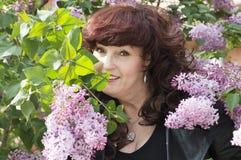 Porträt im Freien der Mittelalterfrau neben einem blühenden lil Lizenzfreie Stockfotografie