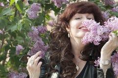 Porträt im Freien der Mittelalterfrau neben einem blühenden lil Stockfotografie
