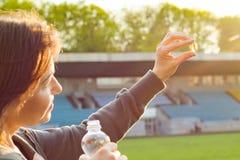 Porträt im Freien der reifen Frau Kapselpille des Vitamins E des Lebertrans, am Stadion einnehmend Lizenzfreie Stockbilder