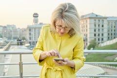 Porträt im Freien der reifen Frau mit Smartphone, Finger auf mit Berührungseingabe Bildschirm, Textnachricht, goldene Stunde stockbilder