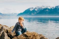 Porträt im Freien des entzückenden kleinen Jungen, der durch den See stillsteht Stockfotos