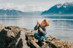 Porträt im Freien des entzückenden kleinen Jungen, der durch den See stillsteht Lizenzfreies Stockfoto