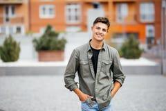 Porträt im Freien des hübschen jungen Mannes, der auf die Straße, Kamera und Lächeln betrachtend geht Stockbilder
