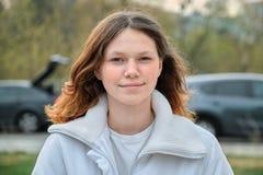 Porträt im Freien des Jugendlichmädchens 15 Jahre alt, Mädchen, das mit dem langen braunen Haar in der weißen Jacke lächelt lizenzfreies stockfoto