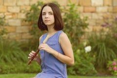Porträt im Freien des jungen Mädchens ein Musikinstrumentrohr spielend lizenzfreie stockfotografie