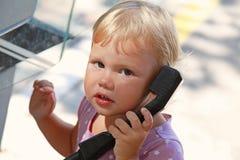 Porträt im Freien des kleinen blonden Mädchens, das am Straßentelefon spricht Stockbild