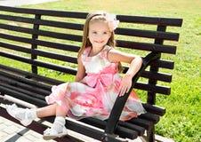 Porträt im Freien des kleinen Mädchens sitzend auf einer Bank Stockfoto
