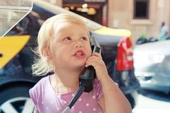 Porträt im Freien des kleinen Mädchens sprechend am Straßentelefon Lizenzfreies Stockfoto