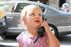 Porträt im Freien des kleinen Mädchens sprechend am Straßentelefon Stockbild