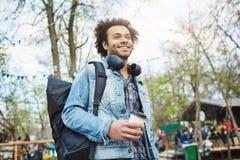 Porträt im Freien des modernen Afroamerikanermannes mit Afrohaarschnitt, tragendem Denimmantel und Rucksack beim Halten stockbilder