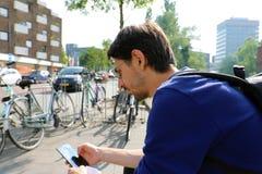 Porträt im Freien des modernen jungen Mannes, der mit Handy in Eindhoven, die Niederlande sitzt lizenzfreie stockfotos