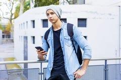 Porträt im Freien des modernen jungen Mannes mit Handy im St. stockfotografie