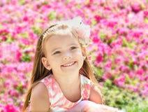 Porträt im Freien des netten kleinen Mädchens nahe den Blumen Stockfotografie