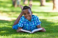 Porträt im Freien des Studentenschwarzjungen, der ein Buch liest Stockfotos