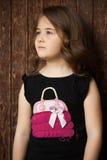 Porträt im Freien einer netten stehenden folgenden Holztür des kleinen Mädchens Stockfoto