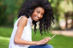 Porträt im Freien eines jugendlichen schwarzen Mädchens, das eine Tasttablette verwendet Stockbild