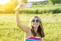 Porträt im Freien eines jungen Jugendlichmädchens, das einen Smartphone für ihr Blog verwendet, und Seiten in den sozialen Netzwe Stockfotos