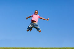 Porträt im Freien eines netten jugendlichen schwarzen Jungenspringens stockfoto
