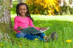 Porträt im Freien eines netten jungen schwarzen kleinen Mädchens, das einen Buh liest Stockfoto