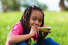 Porträt im Freien eines netten jungen schwarzen kleinen Mädchens, das waterm isst Stockbild