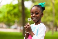 Porträt im Freien eines netten jungen schwarzen Mädchens, das einen Löwenzahn hält stockbilder