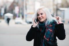 Porträt im Freien eines schönen positiven Mädchens, das am Telefon spricht Lizenzfreies Stockfoto