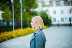 Porträt im Freien von jungen Blondinen, einen Regenmantel tragend Stockfoto
