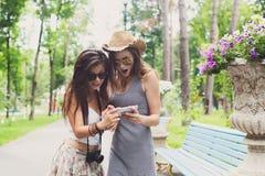 Porträt im Freien von zwei Freunden, die Fotos mit einem Smartphone aufpassen Lizenzfreie Stockfotos