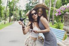 Porträt im Freien von zwei Freunden, die Fotos mit einem Smartphone aufpassen Stockfotografie