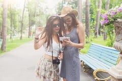 Porträt im Freien von zwei Freunden, die Fotos mit einem Smartphone aufpassen Lizenzfreie Stockbilder