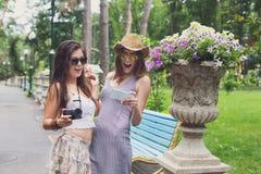 Porträt im Freien von zwei Freunden, die Fotos mit einem Smartphone aufpassen Stockbild