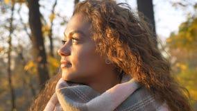 Porträt im Profil des recht gelockten kaukasischen Mädchens, das ruhig leftwards in herbstlichen Park aufpasst stockbild