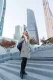 Porträt im vollen Wachstum der blonden Frau stehend auf Leiter Lizenzfreies Stockbild