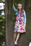 Porträt im vollen Wachstum des Mädchens steht auf den Niederlassungen eines Baums Lizenzfreie Stockbilder